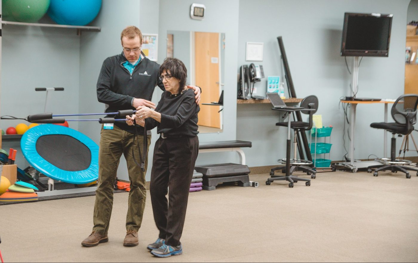 Therapist doing exercise with older patient