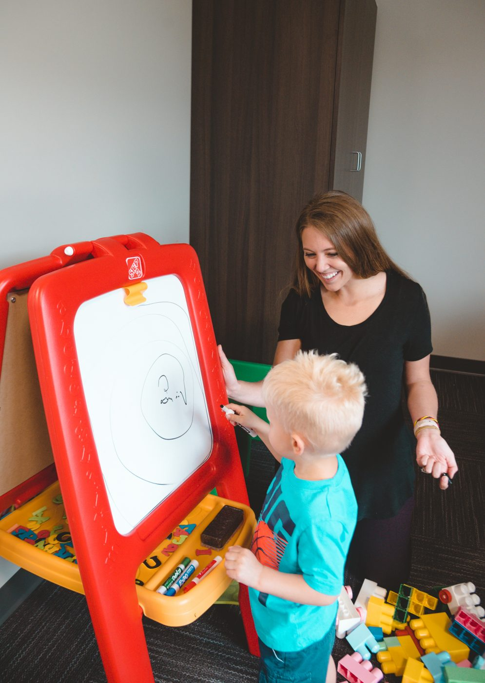 child writing on white board with therapist