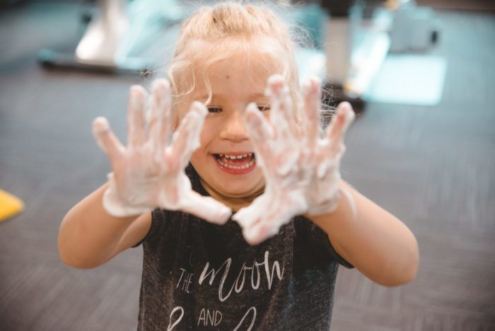 child with shaving cream on hands