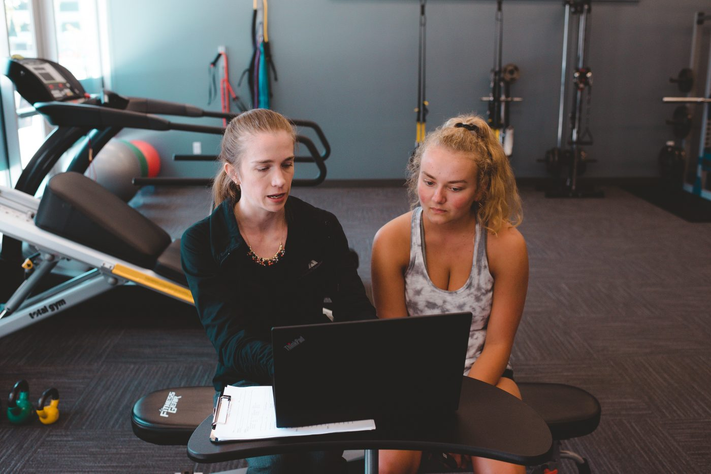 athlete working with therapist by computer