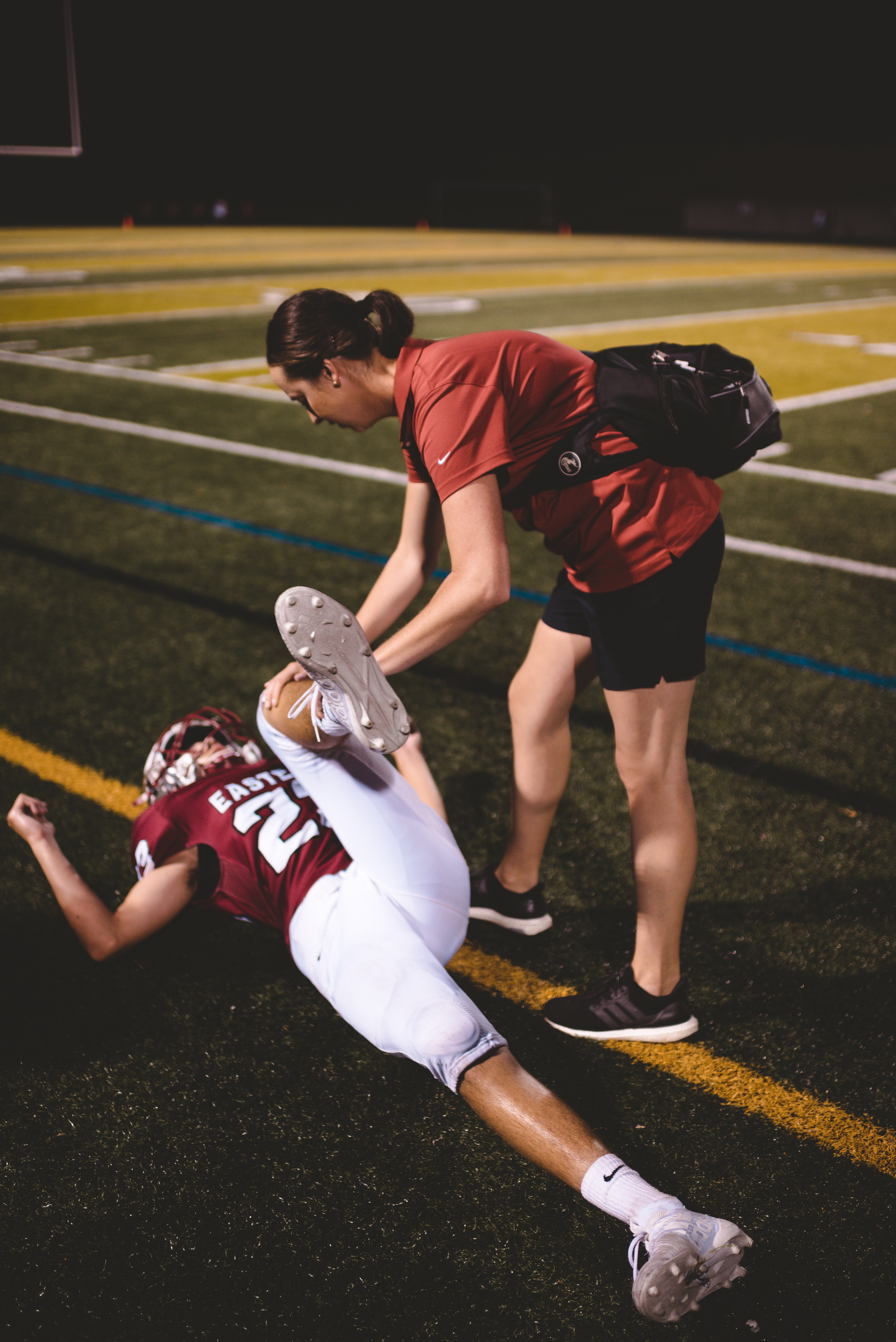 Athlete being stretched by athletic trainer