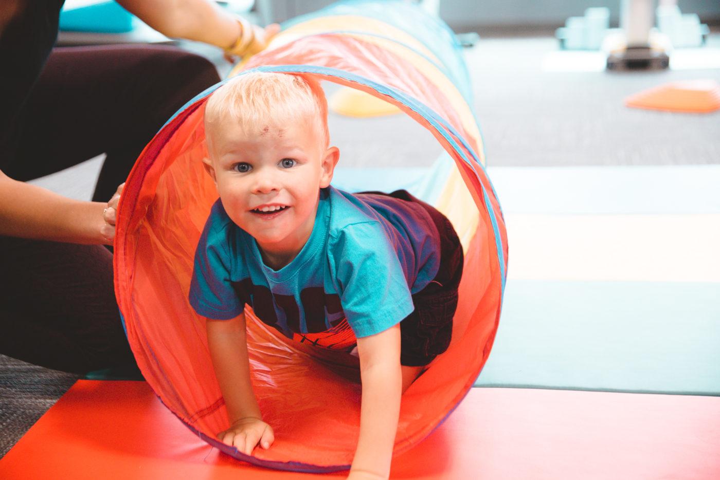Boy climbing through tunnel